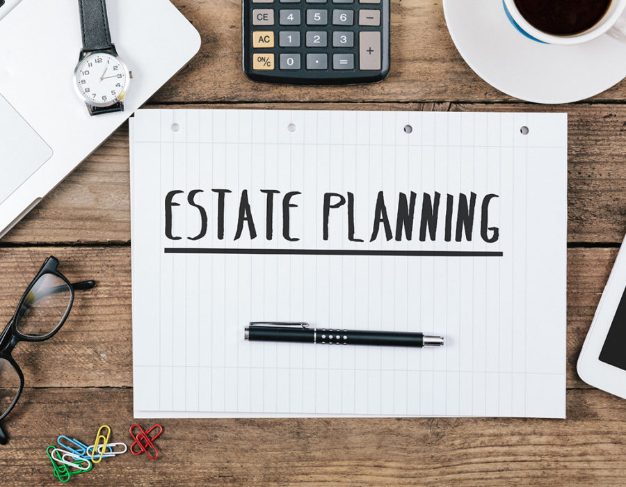 A desk with estate planning written on a piece of paper.