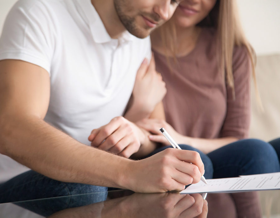 A young couple signs an estate planning document.