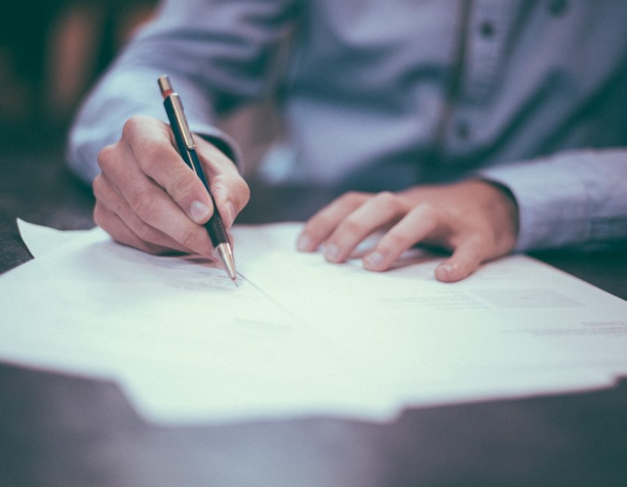 A businessman signs his estate planning documents.