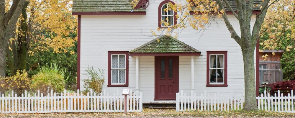 A small white house with a white picket fence.