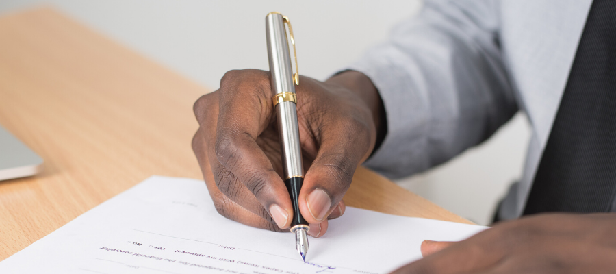 A man signs his estate planning documents.